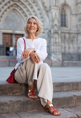 Positive mature woman sits on stone staircase in old city