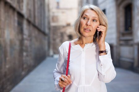 Smiling mature female is walking and talking by phone Reklamní fotografie - 128829972