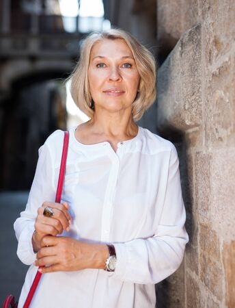 Elegant mature woman is posing in time walking on the street of old city
