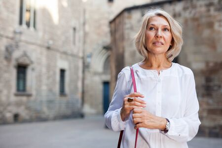 Elegant mature woman is posing in time walking on the street of old city Reklamní fotografie - 128830941
