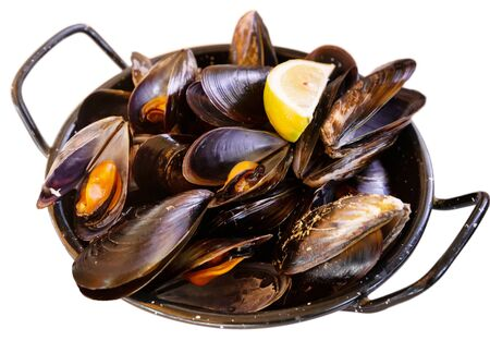 Seafood appetizer. Delicious steamed mussels served with lemon slice in iron pan. Isolated over white background