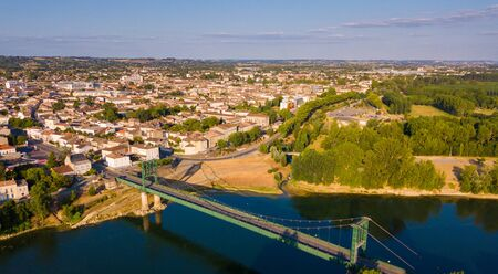 View from drone of small French town of Marmande with suspension bridge over Garonne river on summer day Zdjęcie Seryjne