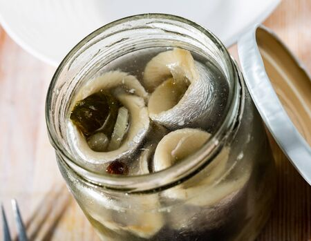 Marinated herring with onions in a glass jar