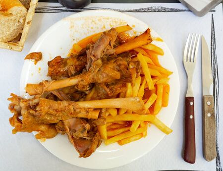 Tasty mutton meat in sauce stewed in oven served with crispy fried potatoes. Spanish cuisine