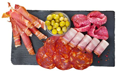 Top view of meat platter - sliced dry-cured jamon, bacon, chorizo and salami on slate serving board with olives