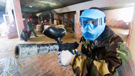 Portrait of blue team happy cheerful positive player who is aiming in opponents on paintball field. Stok Fotoğraf