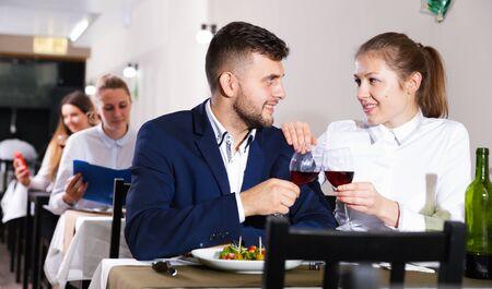 Romantisches Paar isst im Restaurant drinnen zu Abend.
