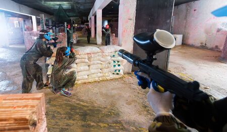 Players are targeting in opponents from barricades on paintball field