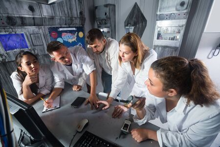 Group of friends are solving quests to get out of escape room stylized like laboratory. Stock Photo
