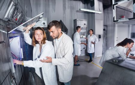 Group of adults trying to get out of the escape room stylized under a laboratory
