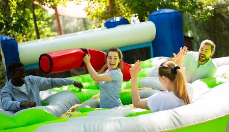 Adults having fun on inflatable playground. Cheerful young woman fighting off her friends with inflatable beam while they hunting for her toy chickens