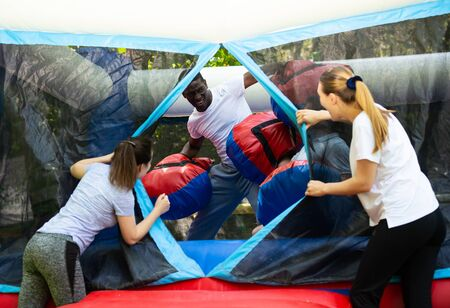 Laughing African American man in big boxing gloves having fun on inflatable ring on adults bouncy playground Stockfoto
