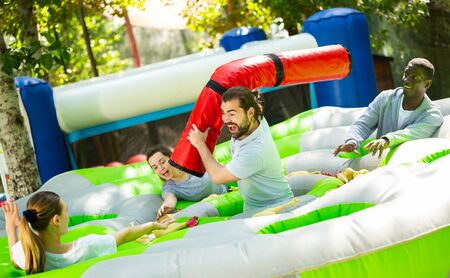 Adults having fun on inflatable amusement playground. Expressive bearded guy fighting off his friends with inflatable log while they trying to filch toy chickens