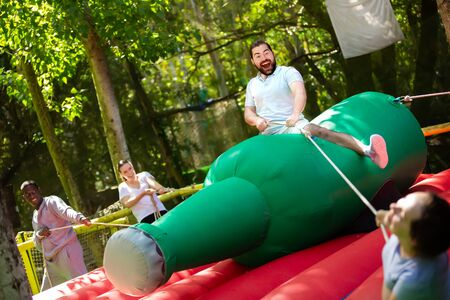 Joyful bearded man saddling inflatable rodeo bottle while other players trying to throw him off