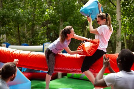 Cheerful adult women having fun on inflatable pillow fight arena in outdoor amusement park