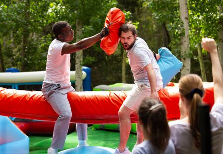 Bearded guy having funny wrestling by pillows on inflatable log with his African friend in outdoor amusement playground