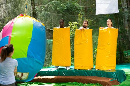 Fine adults dressed in large inflatable pasta pretending to be afraid of being hit by young woman with big bag in amusement park