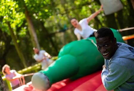Fine African American man pulling rope of inflatable rodeo bottle, trying to throw female friend off in outdoor amusement park