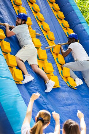 Two adult men having funny competition in climbing on inflatable castle with wooden sticks in outdoor amusement playground