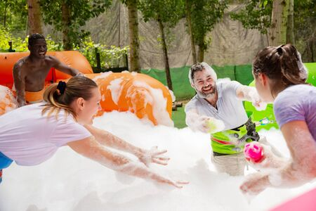 Cheerful friends having fun in outdoor amusement park, picking up balls in inflatable pool full of foam