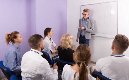 Group of glad students at extension courses together Фото со стока