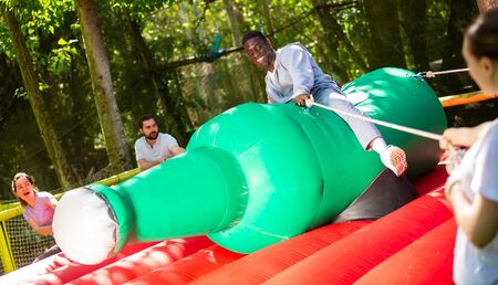 Attraction with a huge inflatable bottle - african-american man trying not to fall from her Reklamní fotografie - 128832325