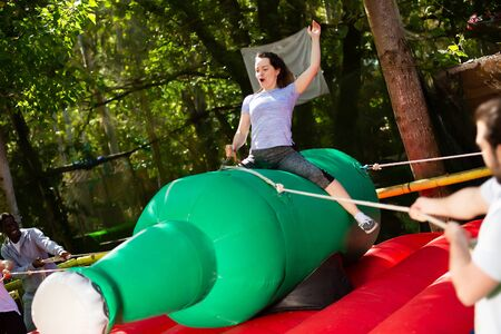 Positive woman trying to stay in saddle on inflatable rodeo bottle while her friends trying to fling her off
