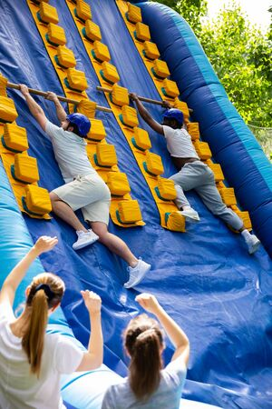 African American man competing with his friend in climbing with wood poles on tall inflatable slide on adults bouncy playground Stockfoto