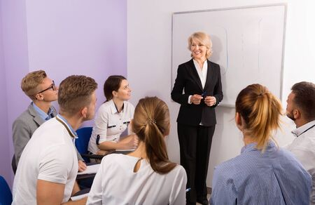 Glad pleasant female speaker giving presentation for smiling students in lecture hall Фото со стока