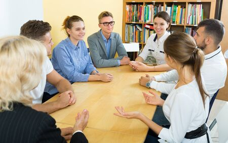 Students doing team study together in  classroom,  sitting at table