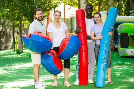 Portrait of happy friends with inflatable logs and pillows at an amusement park Reklamní fotografie - 128832359