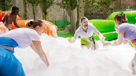 Friendly multiracial team having funny competition in collect of balls in inflatable foam pool on adults bouncy playground Stockfoto