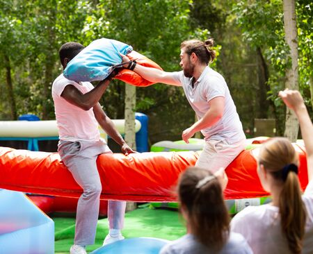 Fun wrestling with pillow in an amusement park on a summer sunny day Imagens