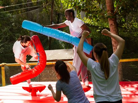 Cheerful adult men having fun on inflatable gladiator fight arena in outdoor amusement park Stockfoto