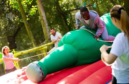 Attraction with a huge inflatable bottle - african-american man trying not to fall from her Stockfoto