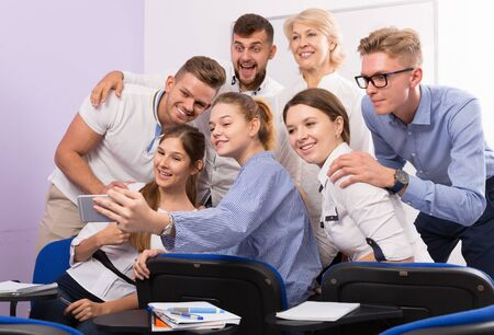Joyful students of different age doing group selfie on smartphone in classroom Stockfoto