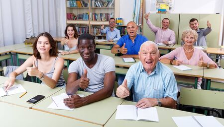 Group different ages satisfied results exam in the  classroom