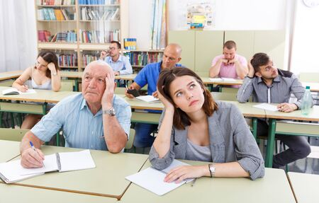Sad students different ages listening task for exam  during business course