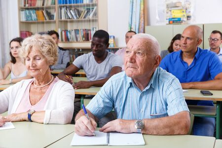 Mature man and woman take a written exam in the classroom