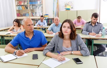 Attentive men and women take a written exam in the classroom