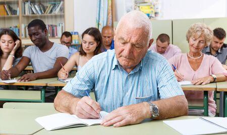 Mature man take a written exam in the classroom Stockfoto
