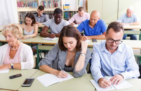Students mixed age listening task for exam in the classroom