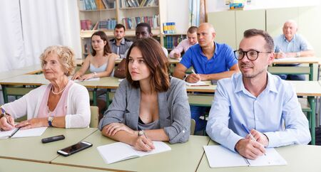 Glad students mixed age listening task for exam in the classroom Фото со стока