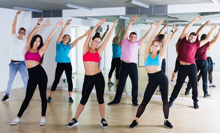 Positive people of different ages studying sport dance elements in dancing hall