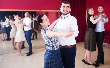 Young dancing couples enjoying foxtrot in dance studio Stock Photo - 128832971