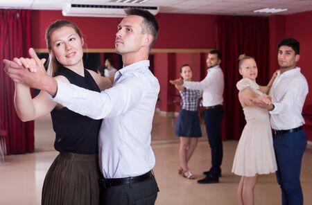 Happy dancing couples enjoying foxtrot in dance studio