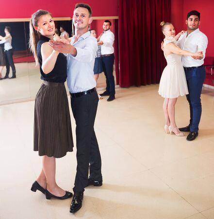 Dancing couples enjoying foxtrot in dance studio Stock fotó
