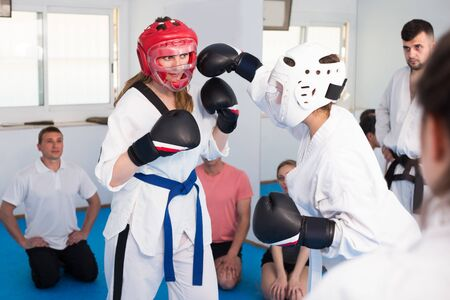 Coach and trainee are sparring in pair to use taekwondo technique during class.