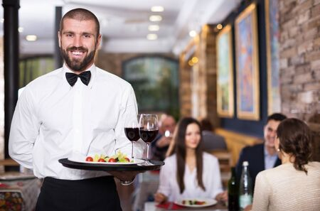 Portrait of smiling waiter with serving tray in the restaurant