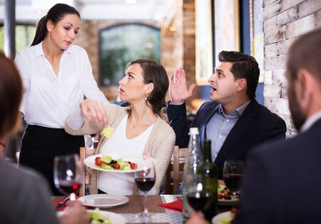 Angry female and male visitors conflict with apologetic waitress about dish in restaurant